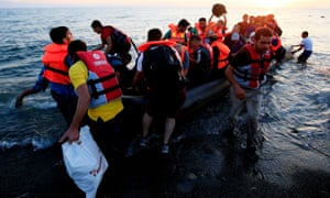 Migrants and refugees in a rubber dinghy arriving on the beach at Psalidi near Kos Town, Kos, Greece