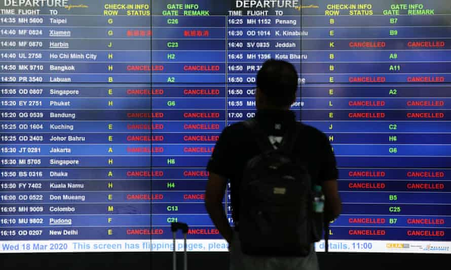 A man looks at an information board displaying cancelled flights after Malaysia's government closed its borders