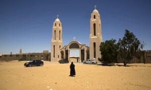 A priest walks in front of the Saint Samuel monastery in Maghagha.