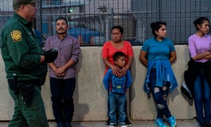 Migrants, mostly from Central America, wait to board a van which will take them to a processing center, in El Paso, Texas, on 16 May.