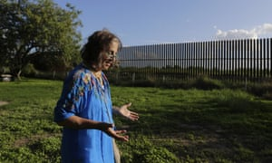 Eloisa Tamez walks in her back yard where the border fence passes through her property, in San Benito, Texas.