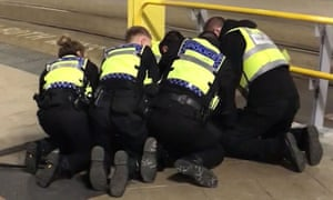 Police restrain a man after three people were stabbed at Victoria Station in Manchester on New Year's Eve.