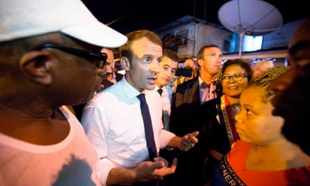 French President Emmanuel Macron meets residents during a visit to the Crique neighborhood, in Cayenne, French Guiana.