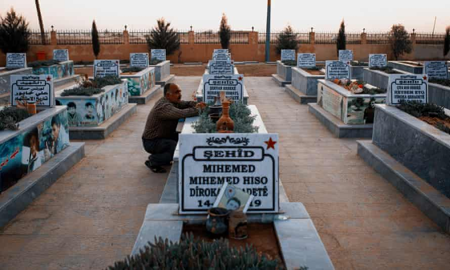 A man visits the grave of his son inside a cemetery for fallen SDF soldiers near the town of Hasakah in north-east Syria.