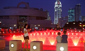 People wearing face masks watch a musical fountain at the People's Square on 2 June 2 in Shanghai, China.