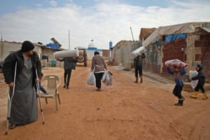 People carry blankets and mattresses at Atma camp
