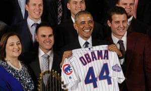 Barack Obama poses with a jersey as he brought the world champion Chicago Cubs baseball team to the White House.