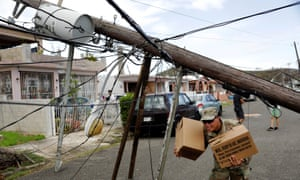A member of the Puerto Rican National Guard dodges downed power cables as he hands out food and water to a neighborhood in Ceiba, Puerto Rico Wednesday.