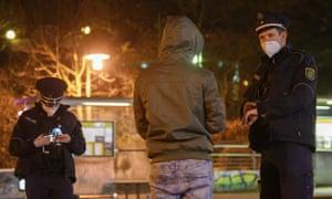 Petugas polisi berbicara dengan seorang pria di distrik Gorbitz di Dresden, Jerman.