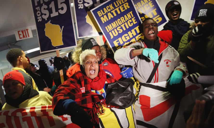 Black Lives Matter and minimum wage demonstrators make their point outside the Democratic debate in Milwaukee on Thursday.
