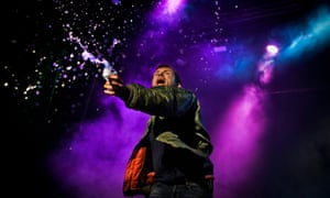 An exuberant Damon Albarn throws water from a bottle while performing on stage