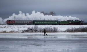 A steam train passes a dam in the Tver region in Ostashkov, Russia