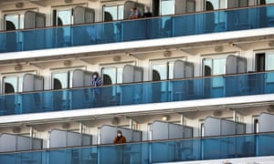 Passengers in masks standing on balconies outside cabins on the Diamond Princess cruise ship
