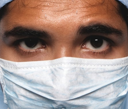 A doctor in a surgical mask with sweat on his brow
