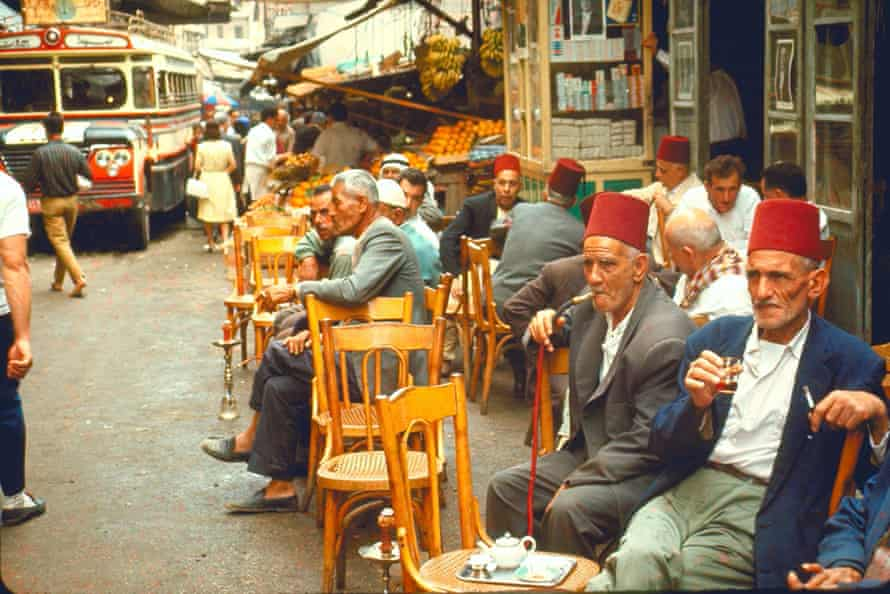 Lebanese men sip tea and smoke traditional narghile pipes at a cafe.