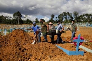 The sons of Veronica Ferreira, 73, who passed away due to the coronavirus, attend her burial at the Parque Taruma cemetery in Manaus.
