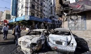 People walk past destroyed cars in Sana''a, Yemen