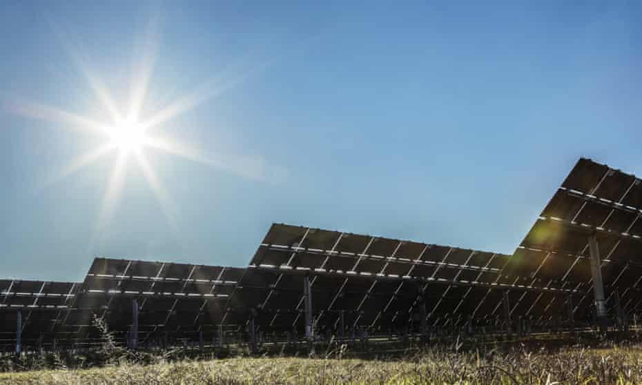 Solar panels at a solar farm with the sun shining overhead