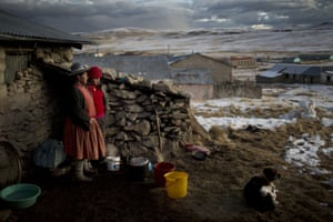 Rosa Carcabusto and her daughter, Maria Luque, stand outside their home before cooking a dinner soup of wheat and dried potatoes in San Antonio de Putina, Peru
