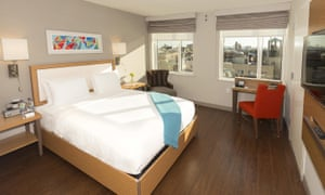A double room at the Edge Hotel in uptown Manhattan. the decor is minimalist with a small writing desk, wooden floor and natural tones. The view out of the window shows Manhattan skyline in bright daylight.