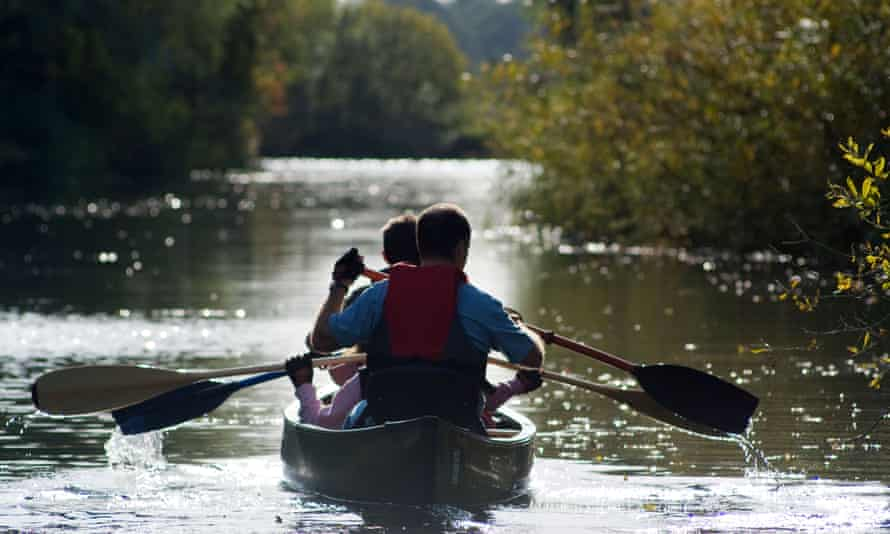 A family paddling a Canadian canoe on the River Waveney near Beccles, UK.