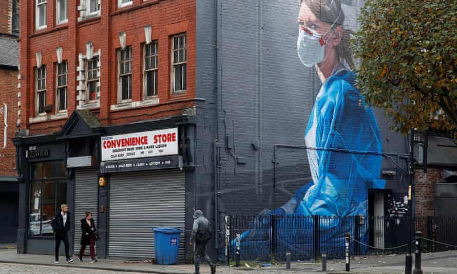 A mural of a masked woman in Manchester.