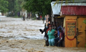People try to cross the overflowing La Rouyonne river in Leogane, south of Port-au-Prince, 5 October 2016