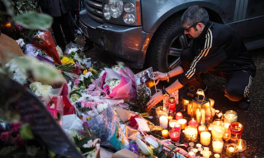 A man places a picture of himself with George Michael among floral tributes outside the singer's home in Highgate