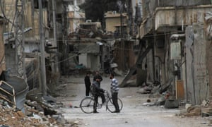 Men chat near buildings destroyed by airstrikes and shelling in Darayya.