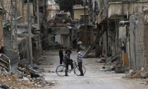 Men chat near damaged buildings in Darayya