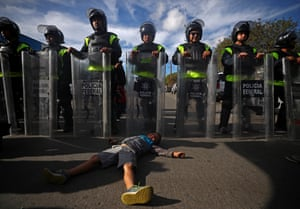 Fernando Velosque, a six-year-old migrant boy from Honduras, part of a caravan of thousands from Central America trying to reach the United States, lies on the ground in front of Mexican riot police outside the El Chaparral port of entry of border, 22 November