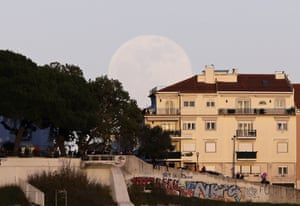 People watch the sunset from the top of a hill as the full moon rises behind them in Lisbon