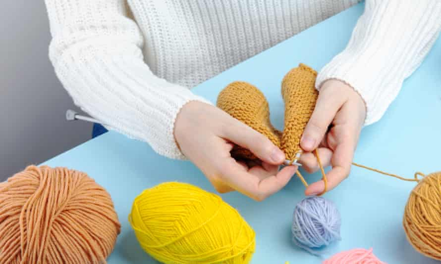 Woman in white sweater knitting yellow yarn clothes