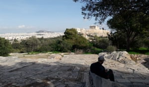 A man taking advantage of being able to exercise outdoors despite a national lockdown in Greece sits within view of the Acropolis.