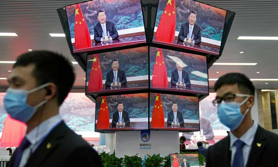 China's President Xi Jinping is seen on screens in the media center as he speaks at the opening ceremony of the third China International Import Expo