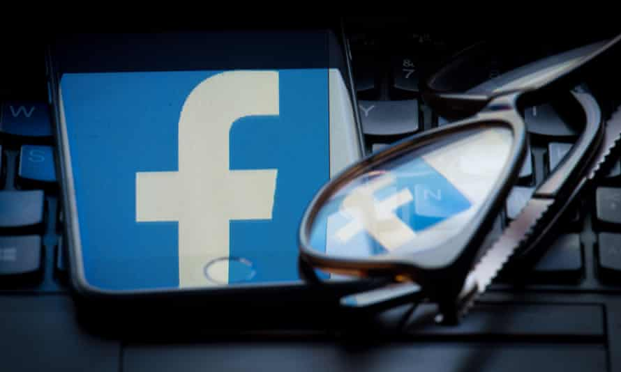 The Facebook logo reflected on the screen of a smartphone resting on a keyboard