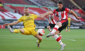 Shane Long of Southampton shoots past Shkodran Mustafi of Arsenal.