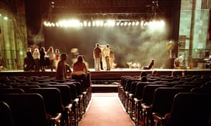 A stage with people on it in a mostly empty auditorium