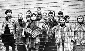 A group of child survivors behind a barbed wire fence at the Nazi concentration camp at Auschwitz-Birkenau in southern Poland, on the day of the camp's liberation by the Red Army, 27th January 1945