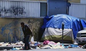 A homeless man walks along a trash-lined street in downtown Los Angeles.