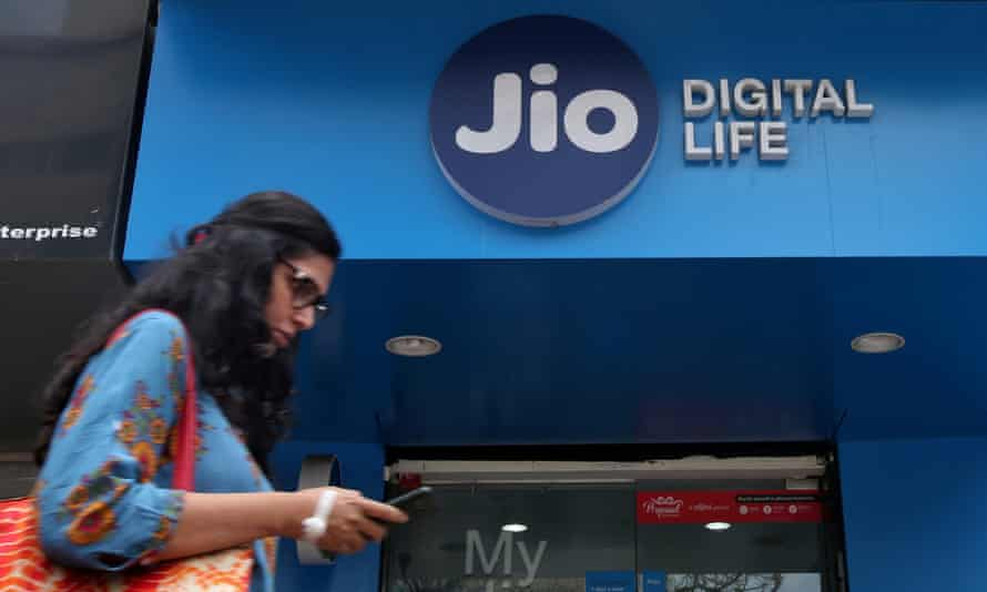 A woman checks her mobile phone as she walks past a mobile store of Reliance Industries' Jio telecoms unit in Mumbai<br>FILE PHOTO: A woman checks her mobile phone as she walks past a mobile store of Reliance Industries' Jio telecoms unit, in Mumbai, India
