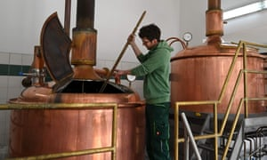Brewer Andreas Weber checks the filling level in a beer brewing kettle in a small brewery in Wolnzach, southern Germany.