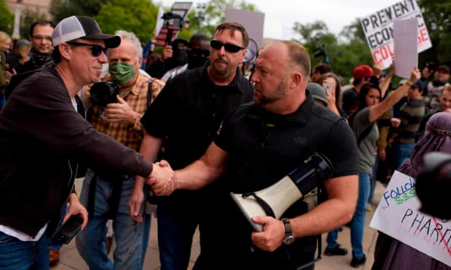 Conspiracy theorist Alex Jones shakes hands during a 'Reopen America' rally in Austin, Texas, on Saturday.