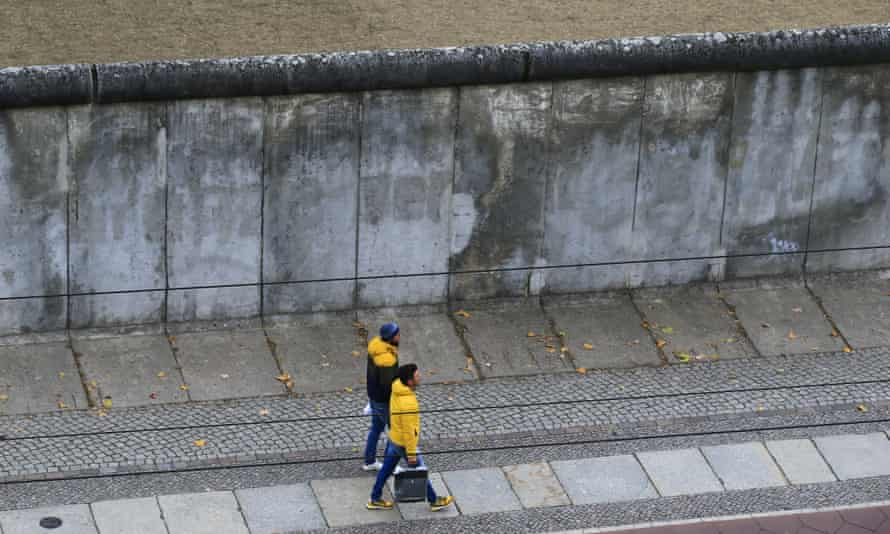 People walk past a remaining section of the Berlin Wall