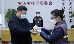 Xi Jinping wears a protective face mask as his temperature is checked in Beijing.