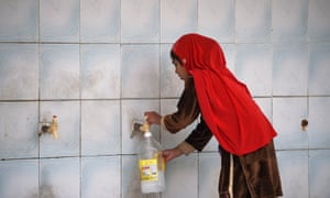 A girl filling a bottle at a water filtration plant in Islamabad.