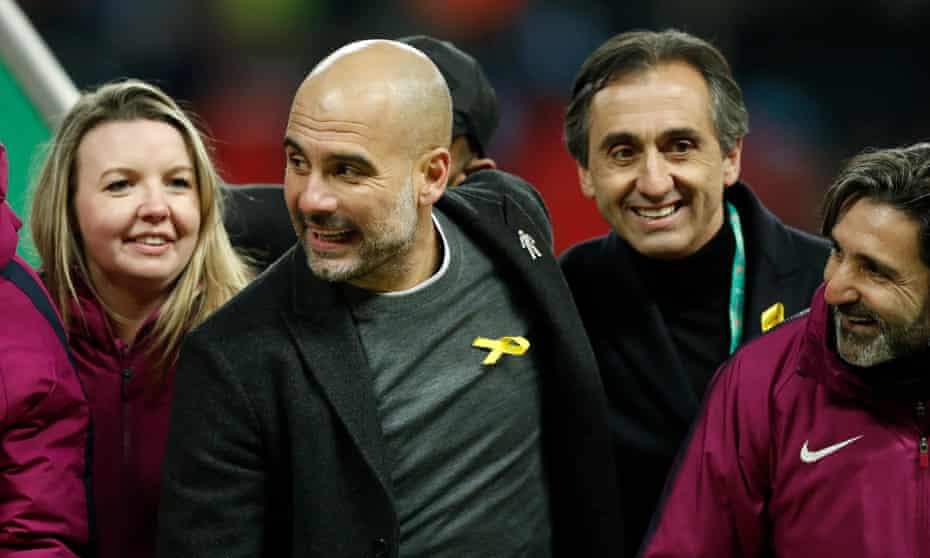Pep Guardiola joins the post-match celebrations while wearing the pro-Catalonia yellow ribbon.