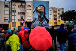Visitors look at a mural by Portuguese artist Nomen