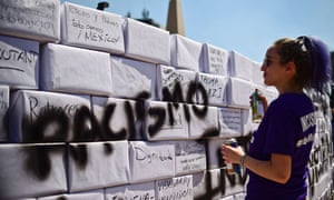 """An activist writes the word """"Racism"""" on a mock wall during an anti-Trump march in Mexico City."""