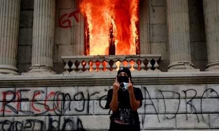 A demonstrator gestures outside the congress building in Guatemala City during clashes between police and protesters.